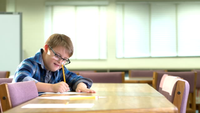 boy with down syndrome in classroom writing - learning disability stock videos & royalty-free footage