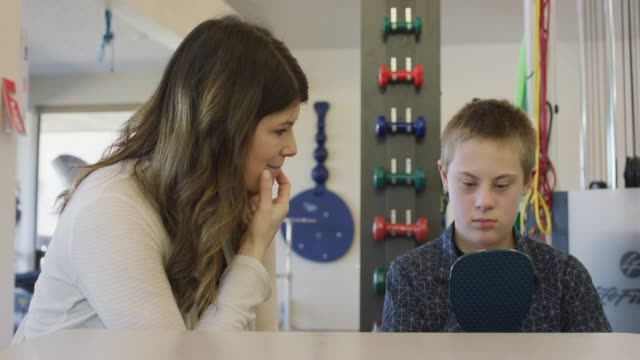 boy with down syndrome uses a mirror during a speech pathology session - sindrome di down video stock e b–roll