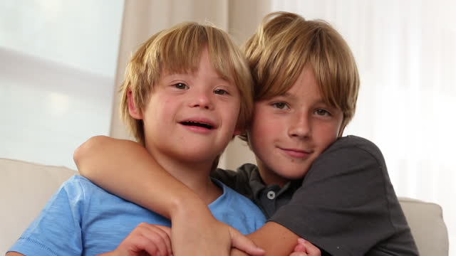 boy with down syndrome with his brother - geschwister stock-videos und b-roll-filmmaterial