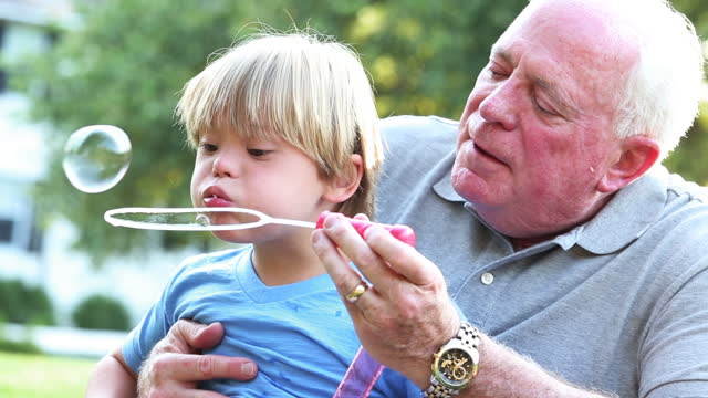 Boy with Down Syndrome with his grandfather blowing bubbles