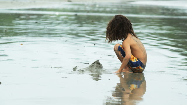 boy with dreadlocks playing in the sand