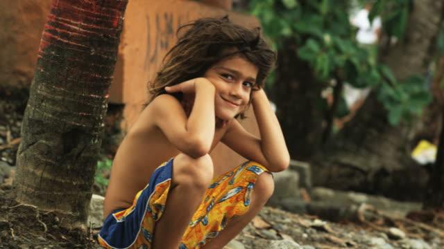 boy with dreadlocks sitting beneath palm trees - swimming shorts stock videos & royalty-free footage