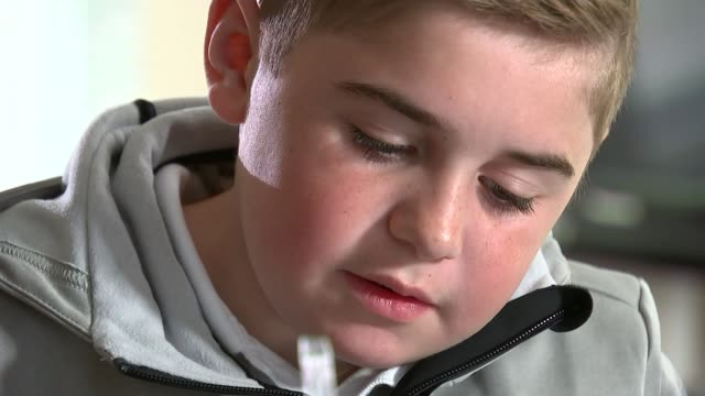 boy with duchenne muscular dystropy mentioned in pmq's england buckinghamshire int gvs archie hill and mother looking at football magazine together... - バッキンガムシャー点の映像素材/bロール