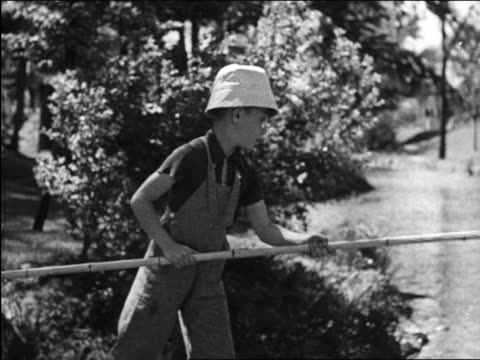 B/W 1948 boy with eyeglasses + hat fishing with bamboo pole / Michigan / medical industrial