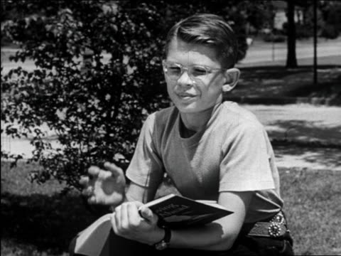 B/W 1948 boy with eyeglasses reading book outdoors + scratching head / Michigan / medical industrial