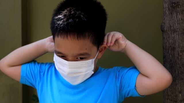 顔のマスクを持つ少年。 - 使い捨て製品点の映像素材/bロール