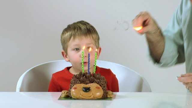 MS SLO MO Boy (2-3) with father blowing out candles on birthday cake / London, UK