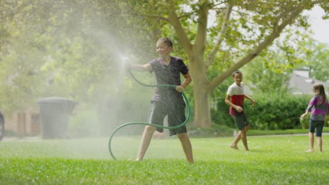 boy with garden hose spraying friends running in grass / provo, utah, united states - 吹きかける点の映像素材/bロール
