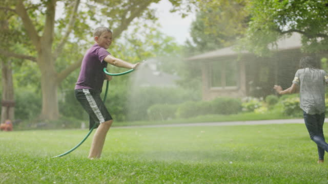 boy with garden hose spraying friends running in grass / provo, utah, united states - provo stock videos & royalty-free footage