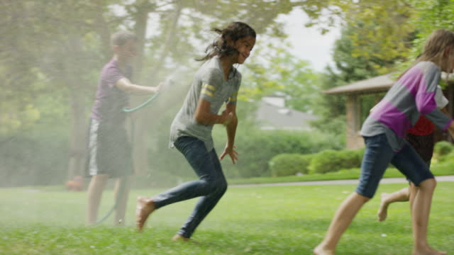 boy with garden hose spraying friends running in grass / provo, utah, united states - wet stock videos & royalty-free footage