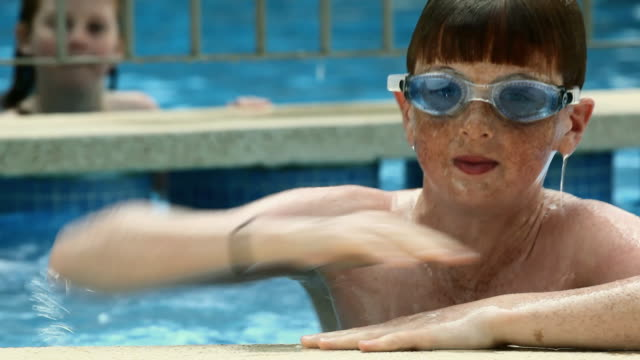 cu boy (12-13) with goggles coming out of pool and smiling, girl (6-7) in background /  palma de mallorca, mallorca, baleares, spain - young girls stripping stock videos and b-roll footage