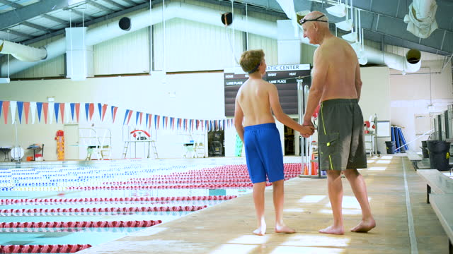 boy with grandfather walking on pool deck holding hands - 10 11 years stock videos & royalty-free footage