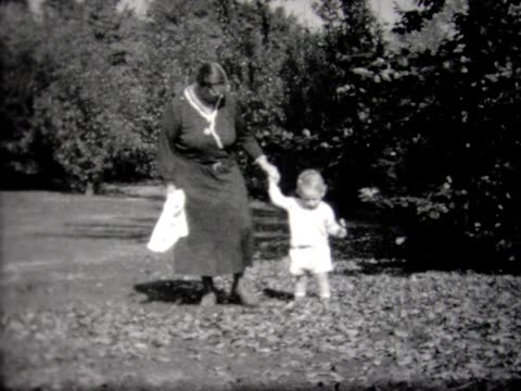 1932 boy with grandma walking in leaves - 1932 stock videos & royalty-free footage