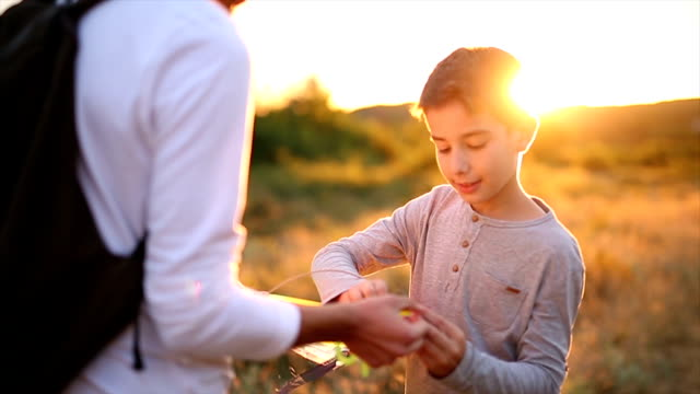 boy with his father prepares to fly a kite at sunset - kite toy stock videos and b-roll footage