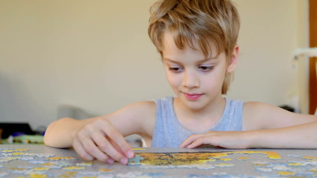 boy with jigsaw puzzles - puzzle video stock e b–roll