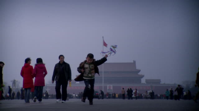 ws boy with kite running on tiananmen square, gate of heavenly peace in background, beijing, china - tiananmen gate of heavenly peace stock videos & royalty-free footage