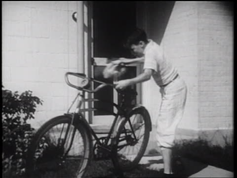 b/w 1939 boy with lunch bag exiting house + jumping on bicycle / documentary - packed lunch stock videos and b-roll footage