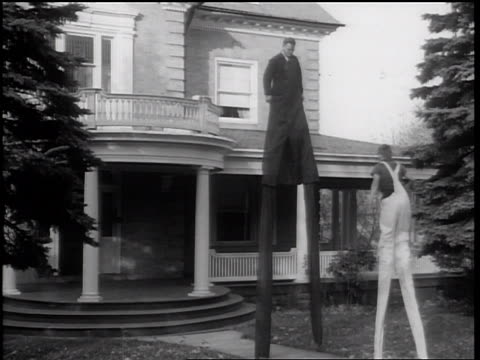 stockvideo's en b-roll-footage met b/w 1938 boy with overalls + stilts walking between stilts of man near house - 1938