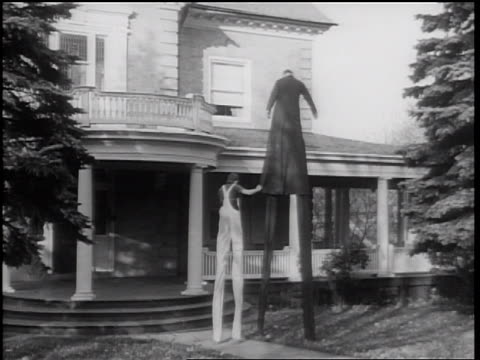 stockvideo's en b-roll-footage met b/w 1938 boy with overalls + stilts walking + holding onto long coat of man with stilts near house - 1938