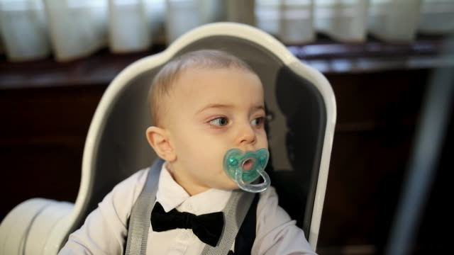 Boy with pacifier sitting in baby chair