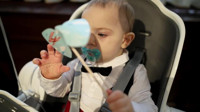 vídeos de stock, filmes e b-roll de menino com o pacificador que senta-se na cadeira do bebê - olhos azuis