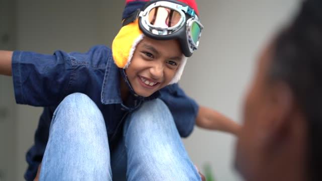 vídeos de stock, filmes e b-roll de o menino com vidros piloto joga a mosca com seu paizinho em casa - fantasy
