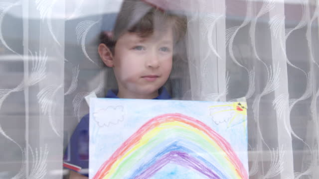 boy with rainbow painting during covid-19 lockdown - prevenzione delle malattie video stock e b–roll