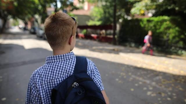 学校から家に帰るスクールバッグを持った少年 - 人の背中点の映像素材/bロール