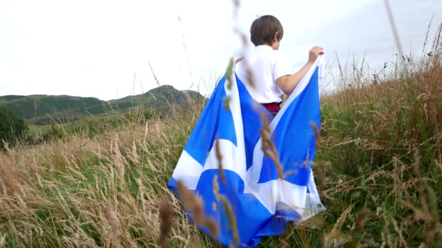 boy with scotland flag on arthur's seat mountain background - scottish culture video stock e b–roll
