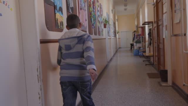 boy with special needs exiting classroom into corridor - un ragazzo adolescente video stock e b–roll