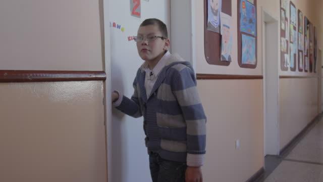 boy with special needs knocking on classroom door - un ragazzo adolescente video stock e b–roll