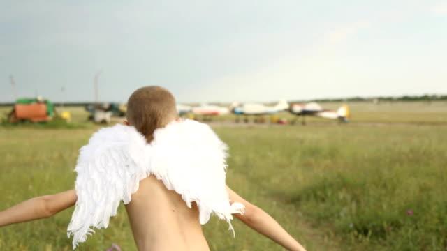 junge mit flügeln auf dem flugfeld - tierflügel stock-videos und b-roll-filmmaterial