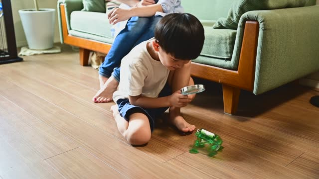 boy working on coding and robotics. he is examining the robot with a magnifying glass. - magnifying glass stock videos & royalty-free footage