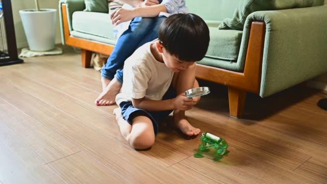 junge arbeiten auf codierung und robotik. er untersucht den roboter mit einer lupe. - vergrößerungsglas stock-videos und b-roll-filmmaterial