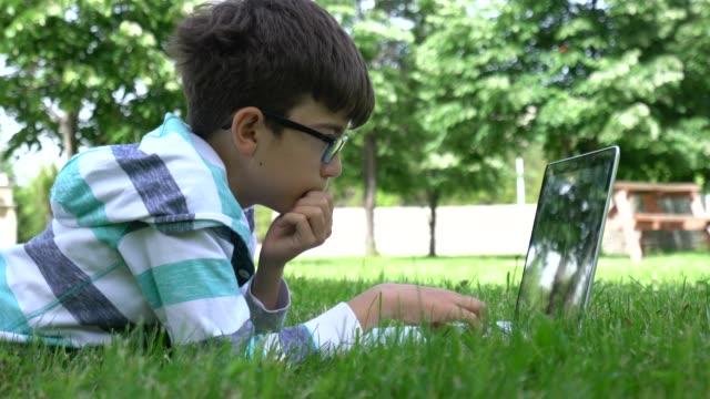 vídeos de stock, filmes e b-roll de menino que trabalha no portátil no campo verde. - parque natural
