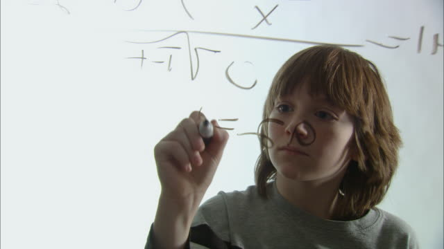 stockvideo's en b-roll-footage met cu boy working on math equation with marker on glass/ new york city - intelligentie