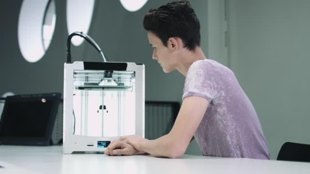 boy working with 3d printer - un ragazzo adolescente video stock e b–roll