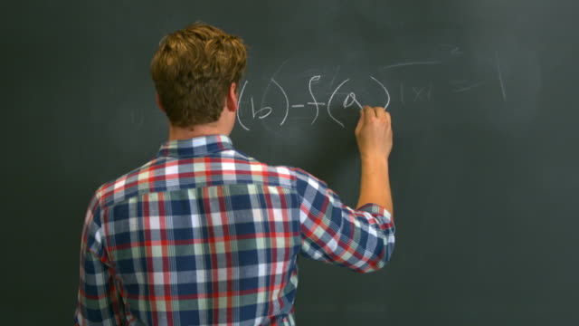 ms boy writing a long math equation on black chalkboard - mathematical symbol stock videos & royalty-free footage