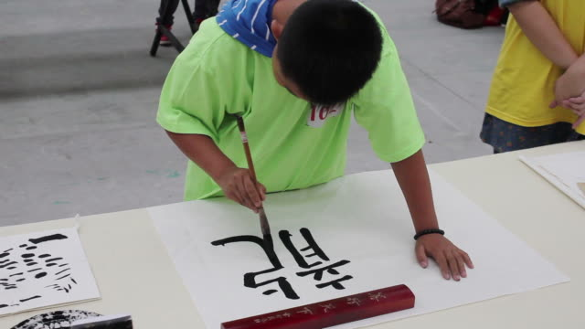 ms boy writing chinese calligraphy in black ink on rice paper/xian,shaanxi,china - washi paper stock videos & royalty-free footage