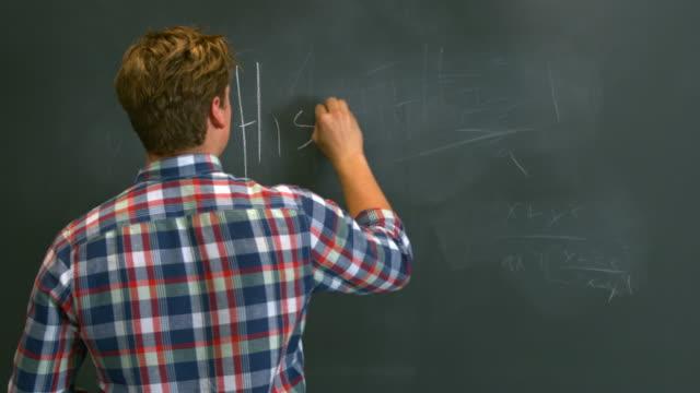 MS Boy writing 'History' on black chalkboard