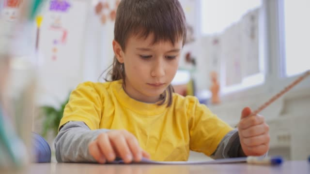 boy writing into his notebook in the bright classroom - one boy only stock videos & royalty-free footage