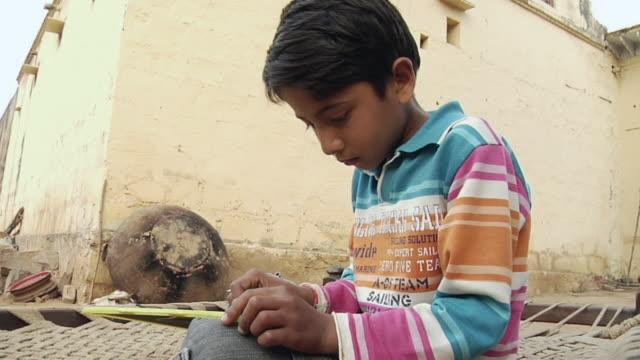 ms boy (8-9) writing on slate / hasanpur, mewat, haryana, india - haryana stock-videos und b-roll-filmmaterial