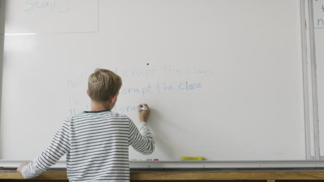 boy writing on whiteboard as detention punishment in classroom / provo, utah, united states - solo un bambino maschio video stock e b–roll