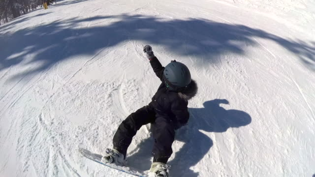 a boy youth child snowboarding at a ski resort. - wintermantel stock-videos und b-roll-filmmaterial