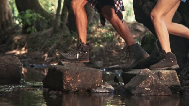 boyfriend and girlfriend crossing river in forest - stepping stone stock videos & royalty-free footage