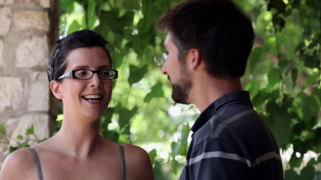CU boyfriend and girlfriend standing on front porch of home leaning in to kiss