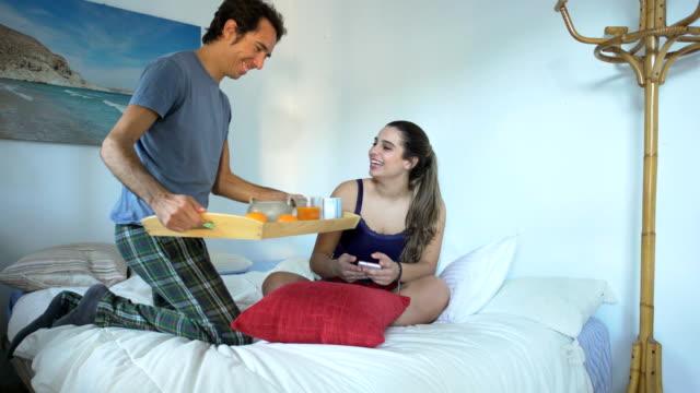 A boyfriend brings the breakfast to his beautiful girlfriend