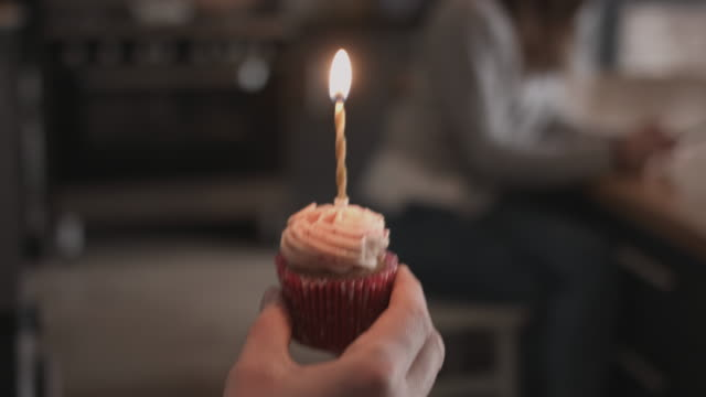 vídeos y material grabado en eventos de stock de boyfriend giving girlfriend a birthday cupcake - candlelight