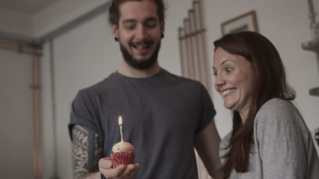 boyfriend giving girlfriend a birthday cupcake - cupcake stock videos & royalty-free footage