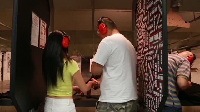 Boyfriend hands an AR-15 assault rifle to his girlfriend at an indoor gun range